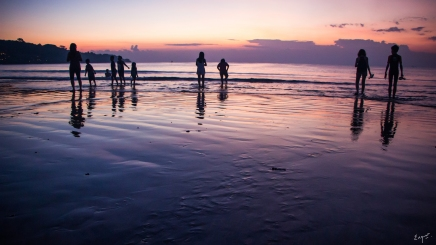 People playing at the beach at sunset