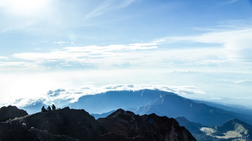 Silhouette of three people with the mountain range and sky as the background taken from the summit of Mt. Rinjani.